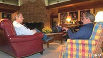 President Bush, right, and British Prime Minister Tony Blair talk at Camp David, Wednesday night, March 26, 2003. Also pictured in background are Chief of Staff Andy Card, rear left, and National Security Advisor Condoleezza Rice.