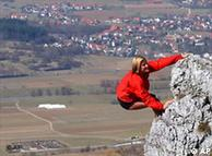 A rock climber hangs on a cliff in Germany