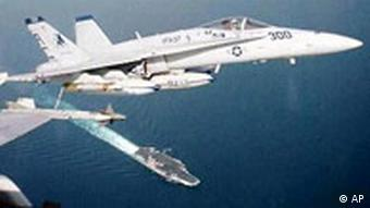 A US Navy F-18C Hornet flies above the US aircraft carrier Enterprise
