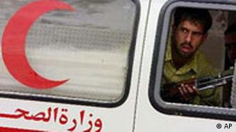 An ambulance guarded by an armed Iraqi man arrives at Saddam City's hospital, outside of Baghdad