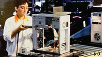 Arbeiterin komplettiert einen Computer in einer Siemens Nixdorf Fabrik