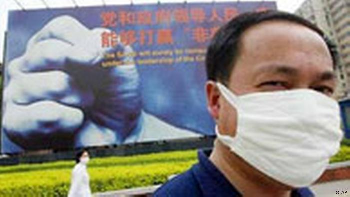 A man wears a mask to protect himself against the SARS virus, in front of a SARS billboard in Beijing Monday May 5, 2003. The billboard reads: The SARS virus will be surely be conquered by our government under the leadership of the Communist Party of China. China's government was criticized by the World Health Organization for initially covering up the SARS crisis and failing to take effective action to prevent it from worsening. (AP Photo/Greg Baker)
