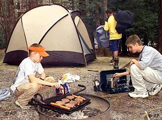 Zwei Jungen grillen vor einem Zelt (Foto: AP)