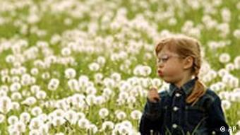 A young girl blows a single dandelion while standing in a field of blooming dandelions