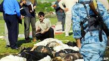 Rescue officials examine the bodies of victims of a bombing attack in the village of Ilaskhan-Yurt about 25 km (15 miles) southeast of Grozny, Wednesday May 14, 2003. Two female suicide bombers blew themselves up Wednesday at a religious ceremony in Chechnya, killing at least 30 people and wounding dozens of others in the second major attack in the breakaway republic in the past three days. (AP Photo/Musa Sadulayev)