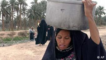 A woman carrying a large pot of water on her head