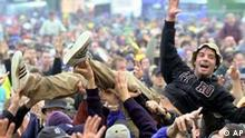 A music fan slam dances over others during a concert of the three-day 'Rock at the Ring' festival at the Nuerburgring, southwestern Germany, Saturday, May 18, 2002. An estimated 50,000 spectators came to watch bands like Lenny Kravitz, Ozzy Ozbourne, Santana and Jamiroquai. (AP Photo/Axel Seidemann)