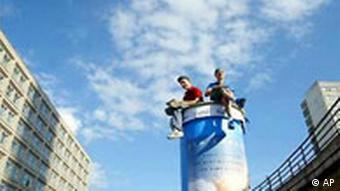 Two men sitting on a tall advertising column in Berlin's Alexanderplatz