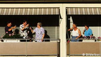 Nachbarn auf einem Balkon prosten sich zu