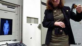 Woman standing next to the full-body scanner machine holding a gun in her hand