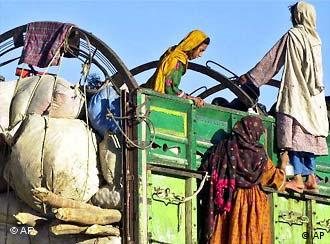 Afghan refugees with carts of possessions