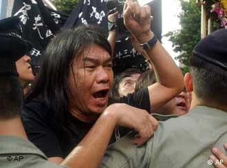 A protester shouts slogans during a protest against a government planned anti-subversion law in Hong Kong Tuesday, July 1, 2003. About 15 protesters tried to get close to a handover anniversary ceremony attended by Chinese Premier Wen Jiabao, Hong Kong Chief Executive Tung Chee-hwa and other officials. But police stopped them and minor shoving matches broke out. (AP Photo/Chan)