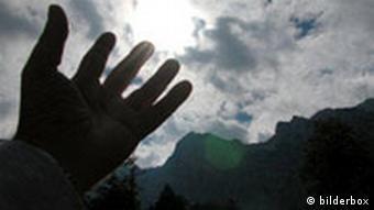 Hand streckt sich gegen den Himmel