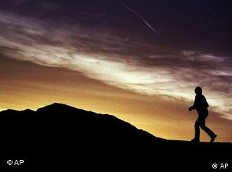 A man in silhouette walks up a hill in Death Valley at sunset