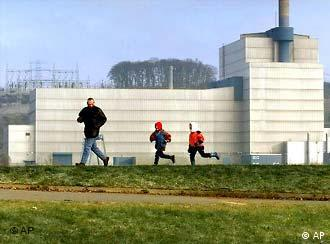 A father and his two children run on the grass outside a nuclear power plant