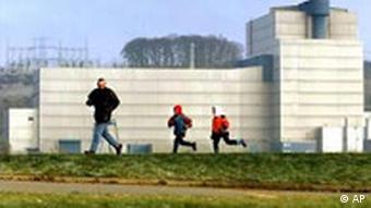 A man and two kids run past a nuclear plant near Hamburg