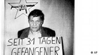 A black and white photo shows Schleyer holding a sign reading: Prisoner for 31 days
