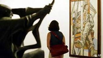 A gallery visitor looks at a painting by Willi Sitte called Arbeitspause (work break) in a display Kunst in der DDR (Art in the GDR) at the Berliner Neuen Nationalgalerie, 24.07.2003. (Photo via AP/Jockel Finck)
