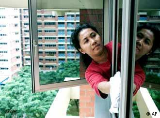 Indonesian maid cleans windows at high rise apartment