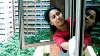 Indonesian maid cleans windows at high rise apartment, Singapore, photo