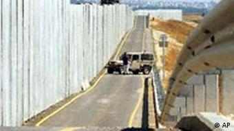 Israeli soldiers patrol along the wall Israel built on the western edge of the West Bank town of Qalqilya Wednesday, June 18, 2003. Palestinian gunmen from Qalqilya bypassed the wall by entering Israel through a water drain and killed an Israeli girl and wounded her sister on Tuesday, just minutes after the Palestinian premier finished a meeting with leaders of militant groups, failing to persuade them to stop attacks. (AP Photo/ Eitan Hess-Ashkenazi)