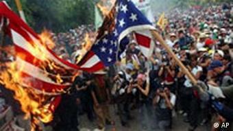 Anti-American protestors burn a US flag