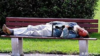 Homeless person sleeping on a park bench
