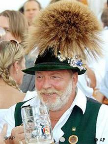 Bavarian in traditional costume holding up a beer glass