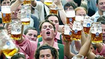 Crowd of people hold up mugs of beer at Oktoberfest
