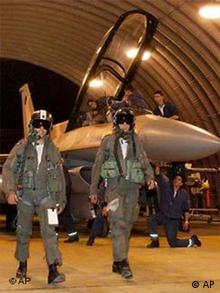 Israel fighter pilots in full flight dress standing in front of an F-16 jet