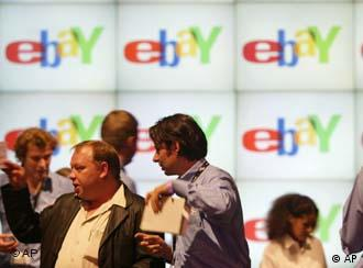 People standing in front of monitors with the eBay logo