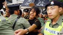 Police officers restrain activist Leung Kwok-hung, center, as he tries to advance towards a venue where Hong Kong's Chief Executive Tung Chee-hwa attends an official flag-raising ceremony marking China's National Day, early Wednesday, Oct. 1, 2003. Some 20 pro-democracy activists scuffled with police while demanding an end to one-party rule by China's Communists. The banner reads: Atrocious regime stinks for 10,000 years. (AP Photo/Anat Givon)