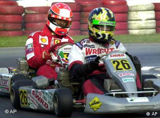 German Formula 1 racer Michael Schumacher, left, touches Britain's Simon Short kart during the qualification race of the CIK-FIA World Karting Championship in Kerpen, western Germany, Saturday, Oct. 27, 2001. Schumacher takes part on the races just for fun. (AP Photo/Hermann J. Knippertz)
